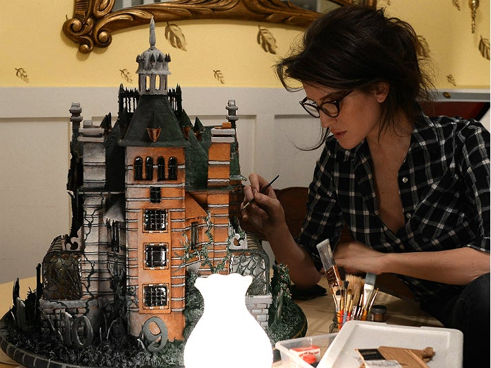 Christine McConnell puts the finishing touches on the Peculiar gingerbread house